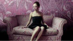 Beautiful Chinese Girl in Black Dress Sitting On Purple Sofa